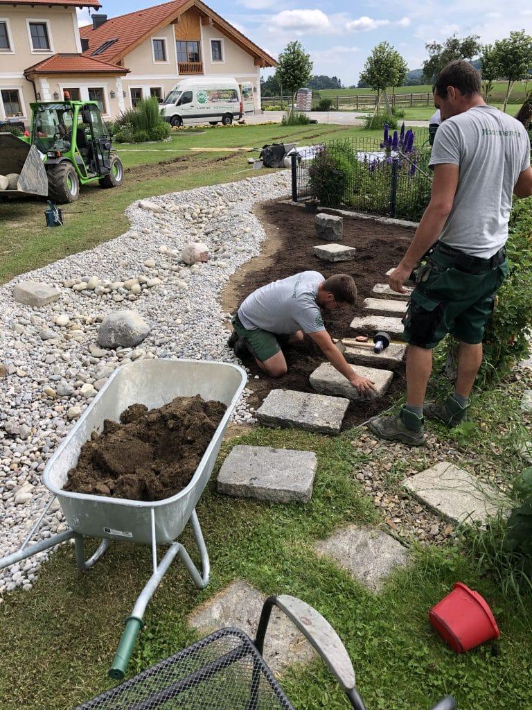Die Gartenprofis des Maschinenring Braunau legen einen Bachlauf im Garten an.
